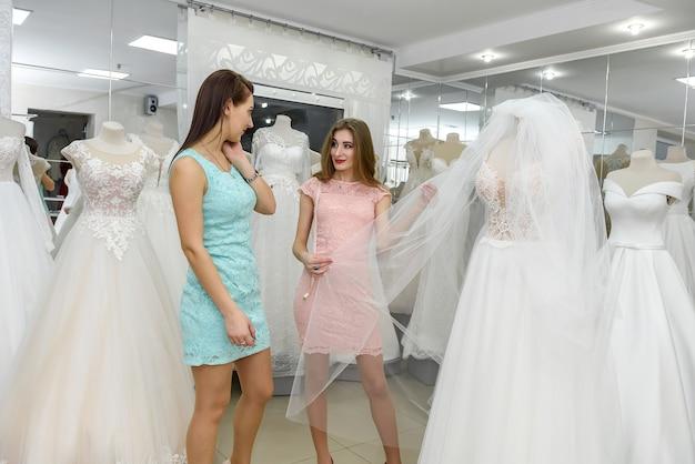 Schöne junge verkäuferin, die einem kunden hochzeitskleid zeigt