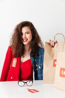 Schöne junge verkaufsfrau, die mit papiereinkaufstaschen sitzt