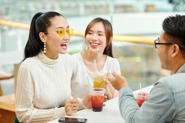 Schöne junge vietnamesische frau, die eistee trinkt und mit freund beim treffen spricht