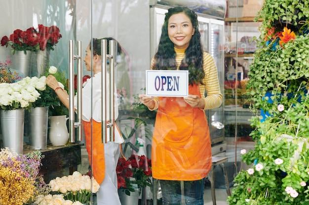 Schöne junge vietnamesische frau, die offenes zeichen auf glastür des blumenladens klebt