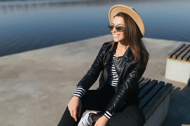 Schöne junge vorbildliche mädchenfrau sitzen auf einer bank im herbsttag am seeufer, gekleidet in freizeitkleidung