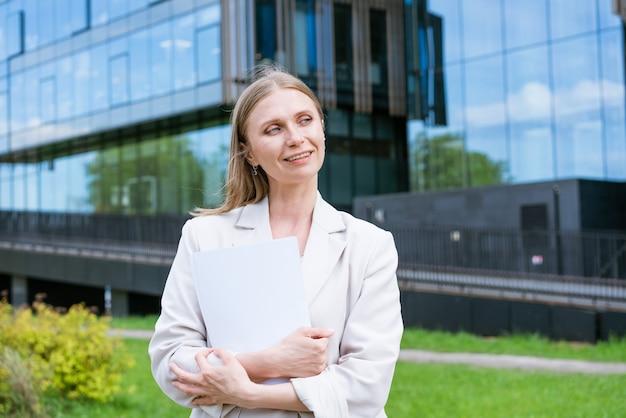 Schöne junge vorstadtgeschäftsfrau, die in klassischen städtischen bürogebäuden mit papierdoku...