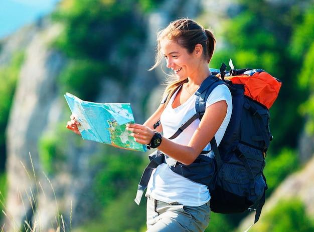 Schöne junge wandererin mit rucksack und karte
