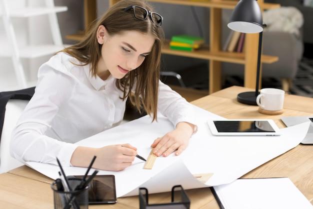 Schöne junge weibliche architektenzeichnungsskizze auf weißbuch über dem hölzernen schreibtisch