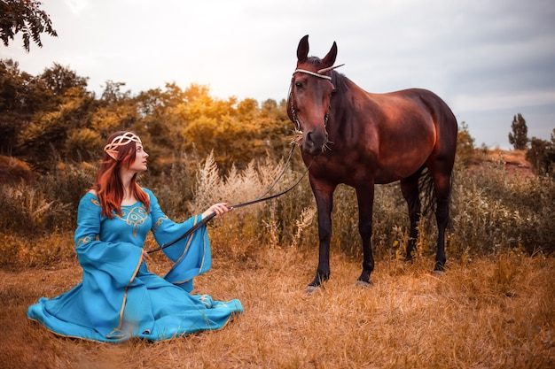 Schöne junge weibliche elfe mit langen dunklen welligen haaren streichelt ihr pferd, das in den waldnymphen des waldes ruht, die ihr pferdepflegehaustier lieben tierharmonieharmonie fürsorglichen besitzer sanften kreaturenmythos streicheln