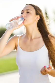 Schöne junge woma trinkwasser auf der straße.
