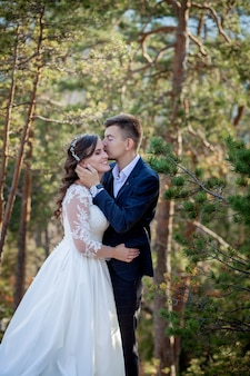 Schöne jungvermählten, die gegen den hintergrund von felsen und von bergen umarmen. stilvolle braut und schöne braut stehen auf der klippe. hochzeitsportrait. familienfoto