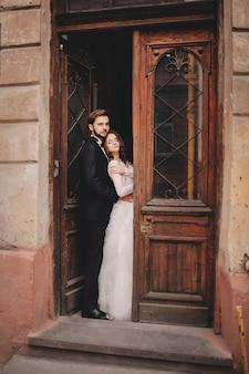 Schöne jungvermählten, die nahe der alten tür umarmen. hochzeitsporträt eines stilvollen bräutigams und einer jungen braut nahe altem haus in einer europäischen stadt.