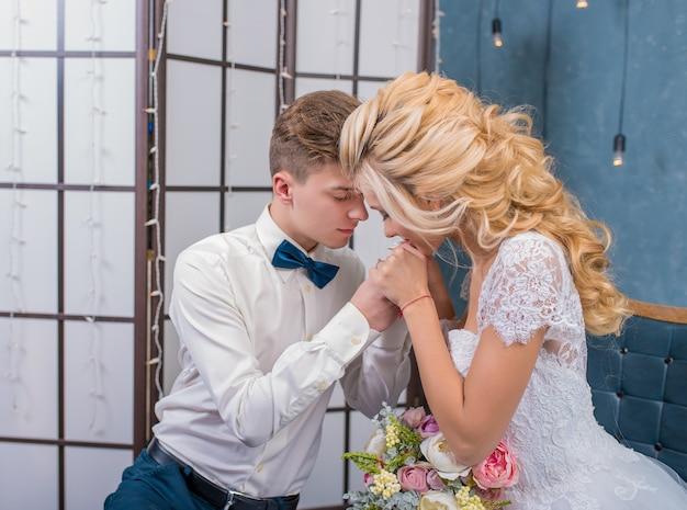 Schöne jungvermählten sitzen und händchen haltend in einem grauen studio.