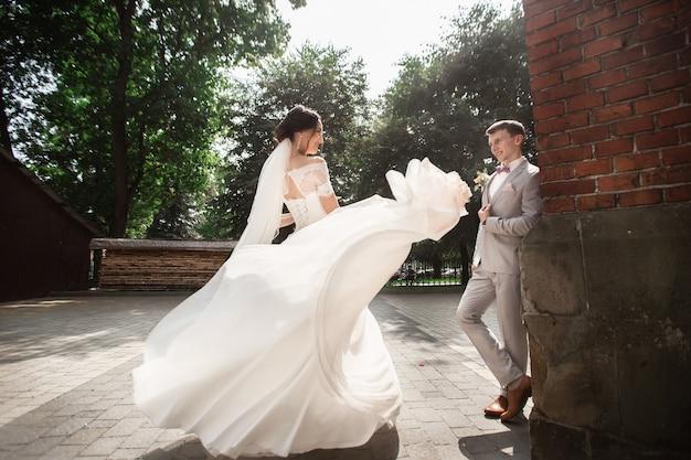 Schöne jungvermähltenpaare gehen nahe alter christlicher kirche