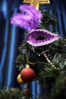 Schöne karnevalsmaske, die am weihnachtsbaum hängt