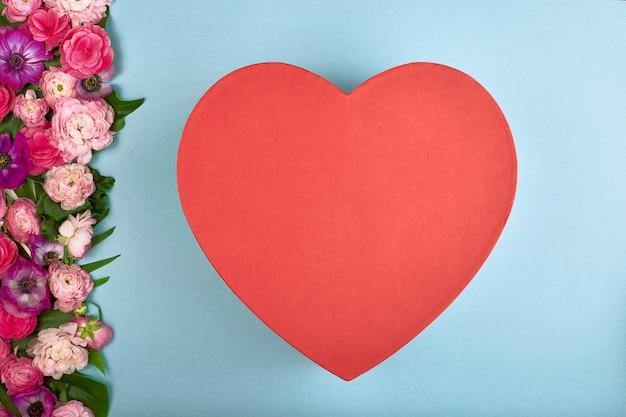 Schöne karte für den feiertag der liebe. hintergrund für den valentinstag. postkarte. rosa blumen auf einem blauen hintergrund und roten herzen für text