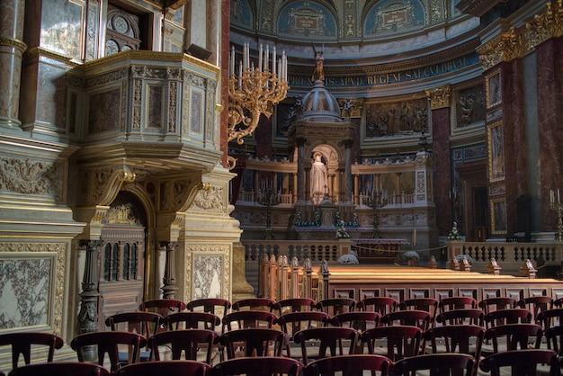 Schöne katholische kathedrale im inneren mit wandmalerei, marmorskulpturen und kirchensitzen in budapest, ungarn.