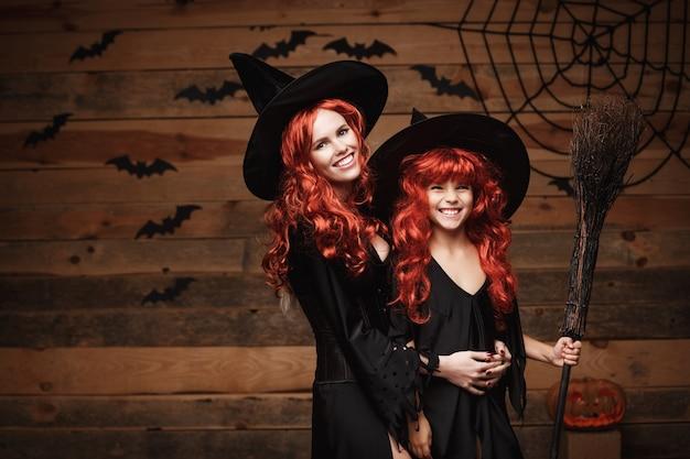 Schöne kaukasisch mutter und ihre tochter mit langen roten haaren in hexenkostüme feiern halloween posiert