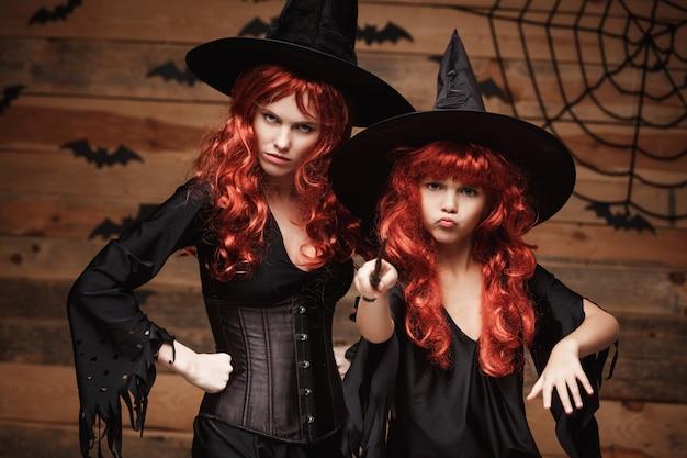 Schöne kaukasisch mutter und ihre tochter mit langen roten haaren in hexenkostümen und zauberstab feiert halloween posiert