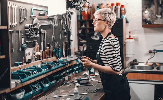 Schöne kaukasische arbeiterin mit kurzen blonden haaren und brillen, die werkzeug von der wand nehmen, um fahrrad zu reparieren. innenraum der fahrradwerkstatt.