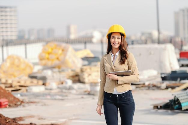 Schöne kaukasische architektin mit langen braunen haaren, zahnigem lächeln und helm auf kopf, die tablette beim gehen auf der baustelle hält.