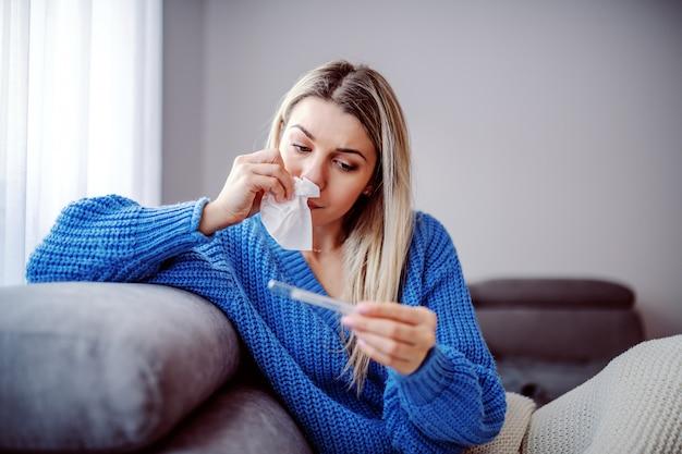 Schöne kaukasische blonde frau im pullover, der thermometer und wischnase beim sitzen auf sofa mit decke bedeckt hält. wohnzimmer interieur.