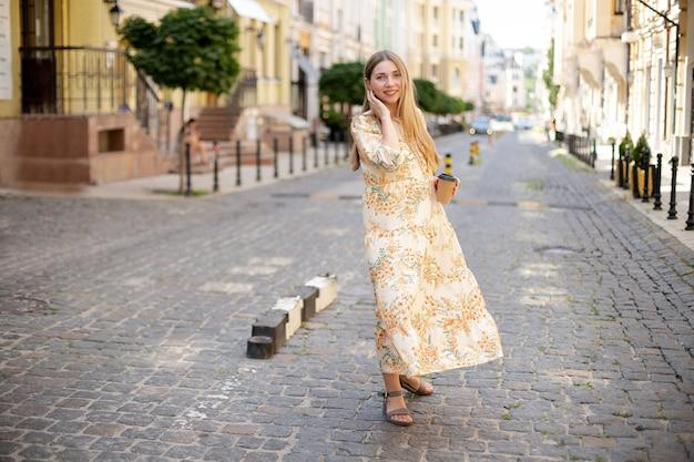 Schöne kaukasische blonde frau in einem kleid mit kaffee zum mitnehmen glättet ihr haar und geht im sommer über das kopfsteinpflaster vor dem hintergrund der straße und der grünen bäume