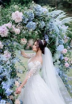 Schöne kaukasische brünette braut steht in der nähe des torbogens aus blauen und rosa hortensien im freien