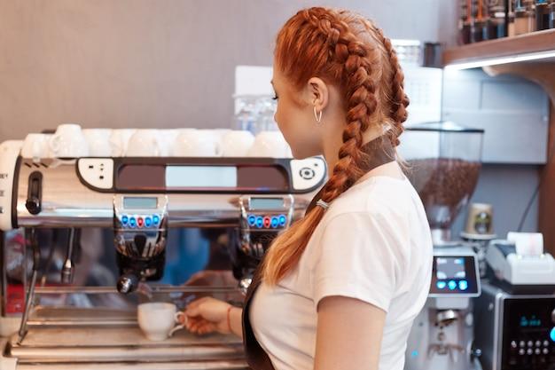 Schöne kaukasische dame lächelnd, die heißen kaffee am modernen kaffeehaus vorbereitet