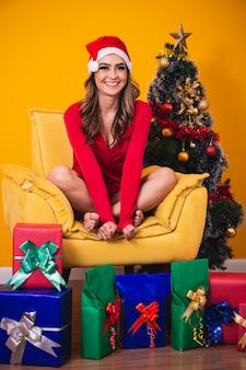 Schöne kaukasische frau auf gelbem hintergrund verkleidet als mama claus mit verschiedenen weihnachtsgeschenken.