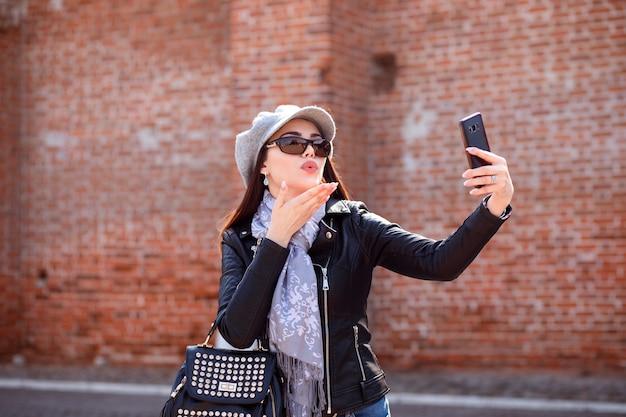 Schöne kaukasische frau bläst einen kuss auf die kamera und macht selfie mit ihrem telefon. im frühling oder herbst im freien.