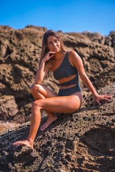 Schöne kaukasische frau, die einen bikini trägt, der auf einem felsen am strand sitzt