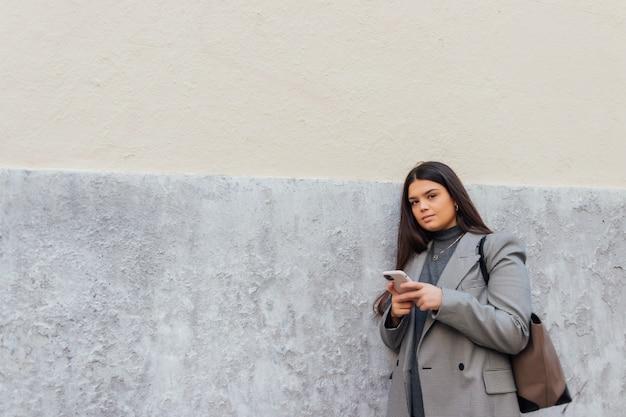 Schöne kaukasische frau, die ihr smartphone benutzt, während sie sich an die wand lehnt