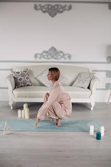 Schöne kaukasische frau, die morgens auf der yogamatte in der nähe des grauen sofas meditiert