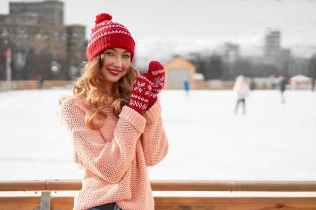 Schöne kaukasische frau, die nahe eislaufbahn winterurlaub steht