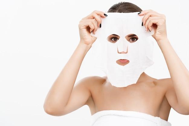 Schöne kaukasische frau, die papierblattmaske auf ihrem gesichtsweißhintergrund anwendet.