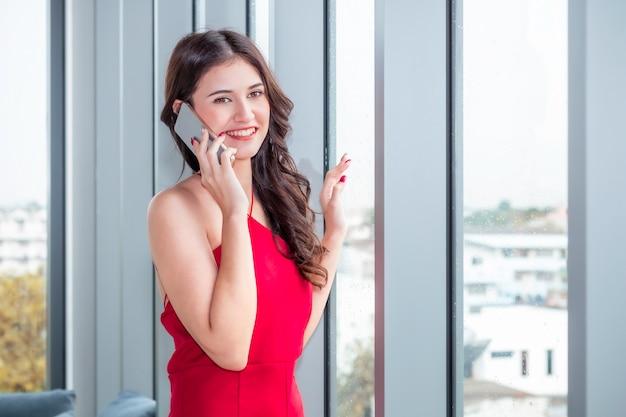 Schöne kaukasische frau, die telefon auf wohnzimmer hält