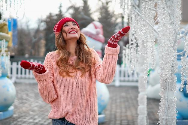 Schöne kaukasische frau, die weihnachtsfestwinterferien steht
