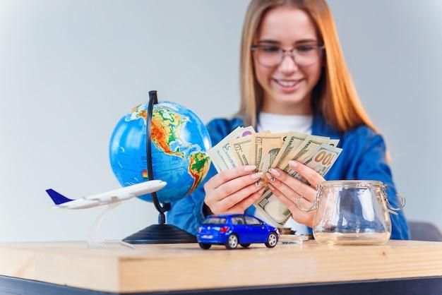 Schöne kaukasische frau im jeanshemd zählt geld für zukünftige reise um die welt und fühlt glück.