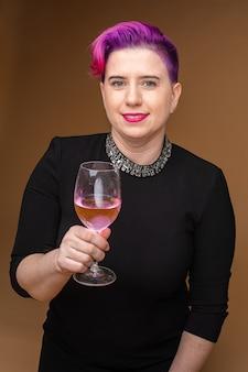 Schöne kaukasische frau im schwarzen kleid hält ein glas roséwein, bild lokalisiert auf brauner wand
