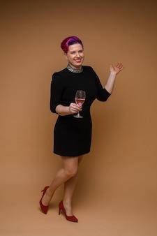 Schöne kaukasische frau im schwarzen kleid hält ein glas roséwein und lächelt, bild lokalisiert auf brauner wand