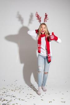 Schöne kaukasische frau im weißen pullover, im roten schal und in den roten handschuhen freut sich, bild