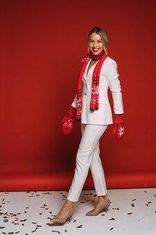Schöne kaukasische frau im weißen pullover, im roten schal und in den roten handschuhen freut sich