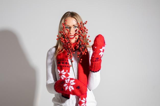 Schöne kaukasische frau im weißen pullover, im roten schal und in den roten handschuhen hält dekorierte blumen