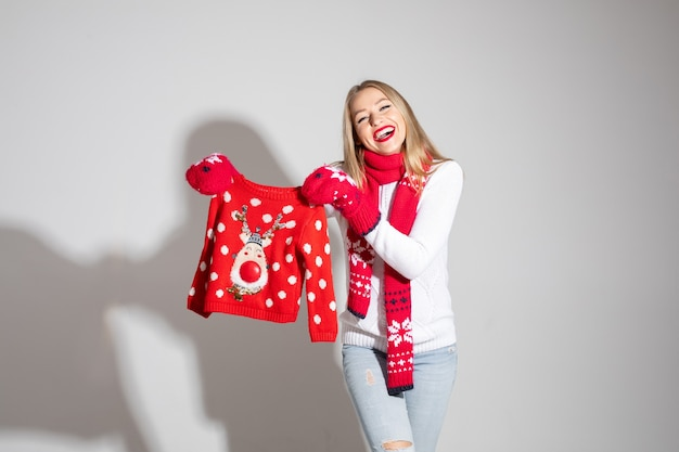 Schöne kaukasische frau im weißen pullover, im roten schal und in den roten handschuhen hält warmen pullover, bild