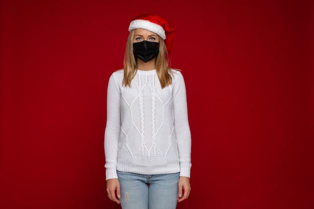 Schöne kaukasische frau im weißen pullover und im weihnachtshut, die angst haben, sich mit dem virus zu infizieren
