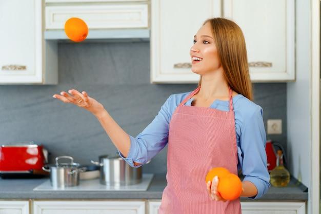 Schöne kaukasische frau in der roten schürze, die reife orangen beim stehen in der küche hält