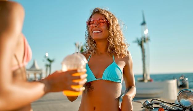 Schöne kaukasische frau in rosa gläsern und einem badeanzug mit limonade oder saft mit ihren freunden am strand im sonnigen tag, ihren urlaub genießend.