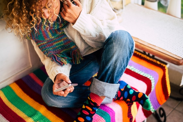 Schöne kaukasische frau lächelt, während sie zu hause auf der terrasse mit einem smartphone eine nachricht sendet