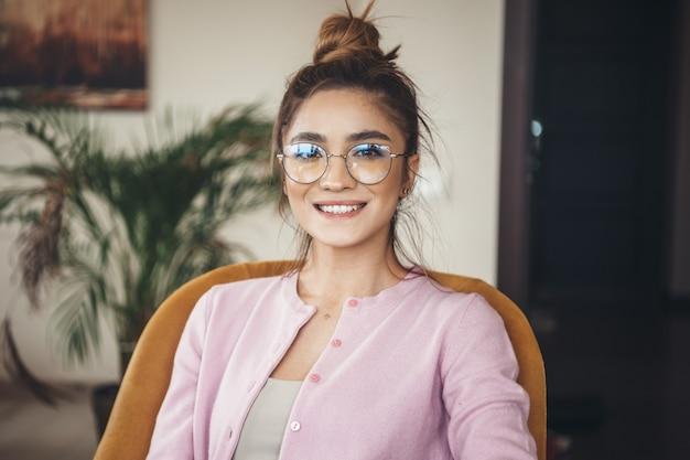 Schöne kaukasische frau mit brillen, die an der kamera zahnig lächeln, während sie eine rosa jacke tragen