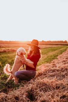 Schöne kaukasische frau mit ihrem netten braunen pudelhund bei sonnenuntergang in der landschaft
