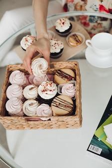 Schöne kaukasische frau mit kurzen dunklen haaren in einem weißen, gemütlichen pullover hält einen süßen marshmallow und lächelt