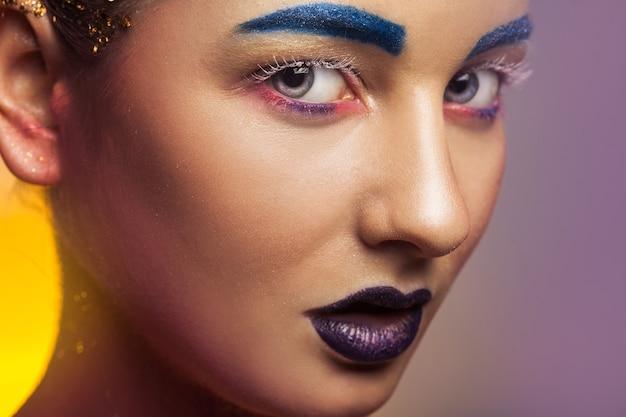 Schöne kaukasische frau mit mehrfarbigem make-up und gesunder haut