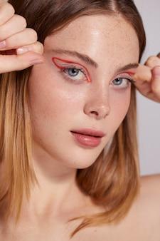 Schöne kaukasische frau mit rotem eyeliner